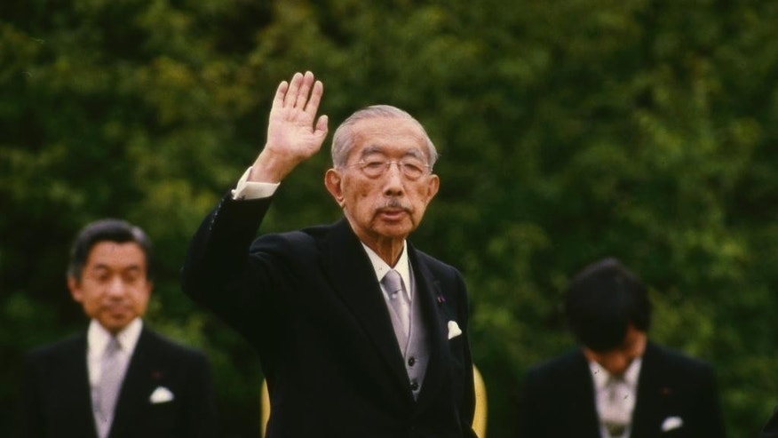 FILE - In this May 19, 1988 file photo, Japanese Emperor Hirohito waves as Crown Prince Akihito, left, looks on during the imperial garden party at the Akasaka Imperial Gardens in Tokyo. Japan's Imperial Household Agency has compiled a 61-volume biography of the former emperor that portrays him as being distressed that he could not stop his country from going to war, according to Japan's Kyodo News agency. Hirohito died on January 7, 1989. (AP Photo/File)