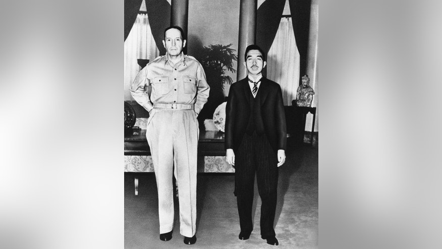 In this Sept. 27, 1945 file photo, Gen. Douglas MacArthur, left, poses with Japan's Emperor Hirohito during the latter's visit to the U.S. Embassy in Tokyo for their first meeting. Japan's Imperial Household Agency has compiled a 61-volume biography of the former emperor that portrays him as being distressed that he could not stop his country from going to war, according to Japan's Kyodo News agency. The 12,000-page record also cites MacArthur, who led America's postwar occupation of Japan, as saying Hirohito had said he accepted full responsibility for the war. (AP Photo/File)