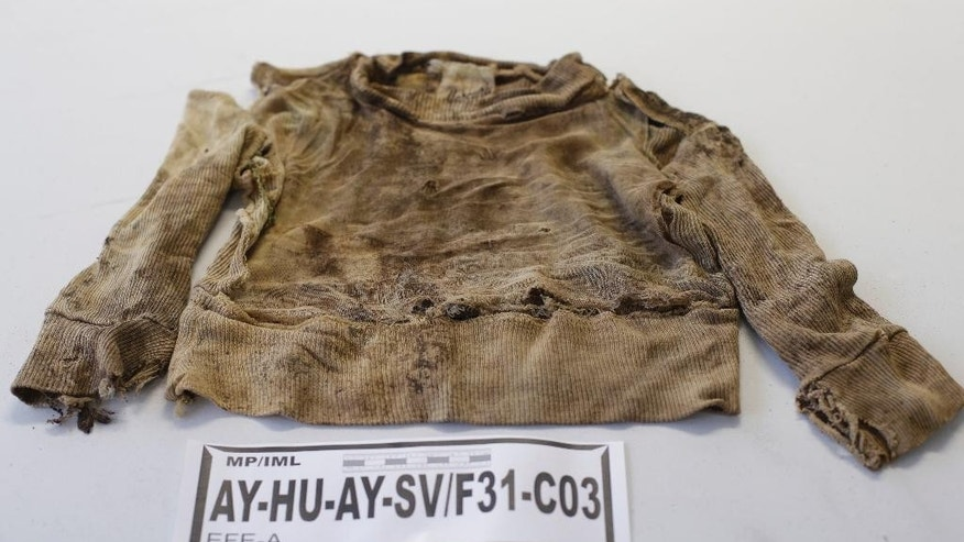 A shirt that belonged to a person who was exhumed from a mass grave at the Los Cabitos army base in Ayacucho province is displayed for the press at the Public Ministry in Lima, Peru, Tuesday, Sept. 9, 2014. According to prosecutors, the clothes displayed on Tuesday belonged to 53 civilians who were allegedly slain by soldiers during Peru's two-decade-long conflict that claimed nearly 70,000 lives. Government prosecutors have opened one case against soldiers who worked at the Los Cabitos army base base between 1983 and 1996. (AP Photo/Martin Mejia)