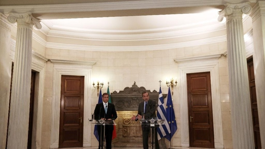 Greek Prime Minister Antonis Samaras, right, speaks as his Portuguese counterpart Pedro Passos Coelho listens during statements to the media at the Maximos Mansion in Athens on Tuesday, Sept. 9, 2014. Coelho is expected to discuss post-bailout growth strategies with Greek officials. (AP Photo/Thanassis Stavrakis)