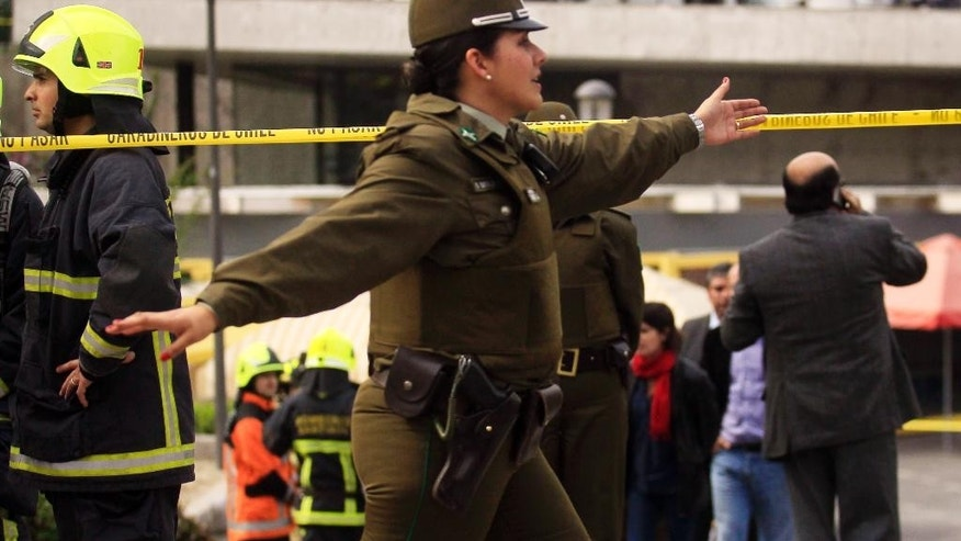 A police officer directs the curious away from a blast site at a subway station in Santiago, Chile, Monday Sept. 8, 2014. A bomb exploded in the Chilean subway station injuring at least seven people, the most damaging in a string of bombs planted around the country's capital this year. (AP Photo/ Luis Hidalgo)