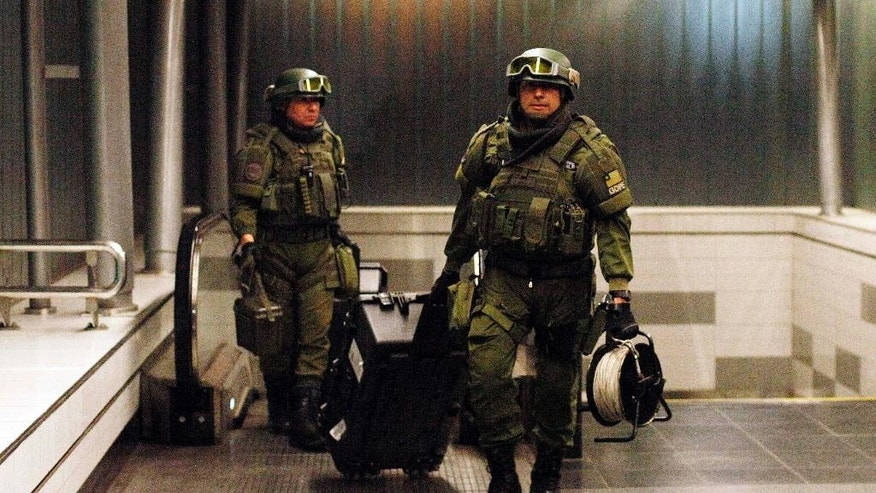 Police explosives experts, walk out of a subway station after a false alarm bomb alert in Santiago, Chile, Wednesday Sept. 10, 2014. President Michelle Bachelet boosted security at subway stations and elsewhere and has said she will use the country's tough, dictatorship-era terrorism laws, after Santiago was rattled by a series of low powered bombings. (AP Photo/ Luis Hidalgo)
