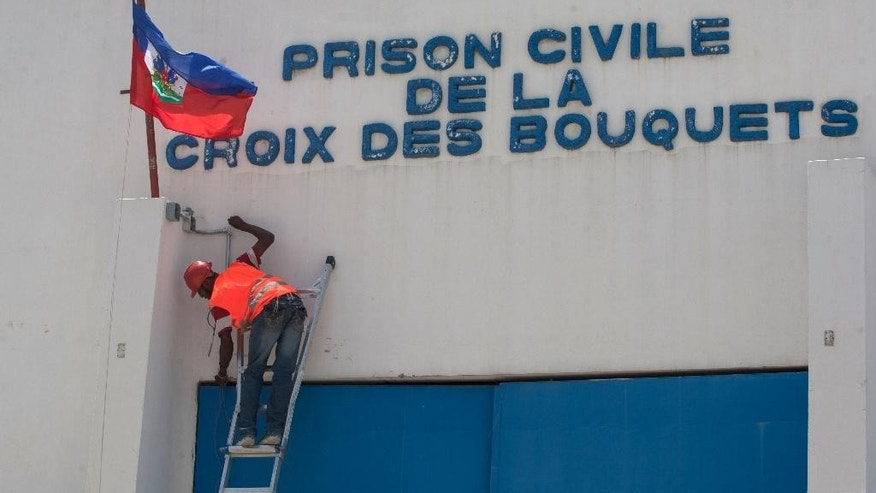 In this Sept. 3, 2014 photo, a technician drills cable for a camera control through the principal gate of the main prison in Croix-des-Bouquets, Haiti. At the prison steps are being taken to improve security. Workers have started to lay down wiring for security cameras at the prison, and officials say they soon will place ankle monitors on the most dangerous inmates there, a plan they say will be implemented in other prisons as well. (AP Photo/Dieu Nalio Chery)