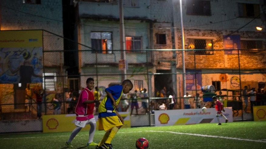Children play soccer at the newly installed pitch powered by their footsteps at the Morro da Mineira favela, in Rio de Janeiro, Brazil, Wednesday, Sept. 10, 2014. Billed as Brazil's first player-powered soccer pitch, the field harnesses the kinetic energy of players' movements to provide nighttime illumination. (AP Photo/Silvia Izquierdo)