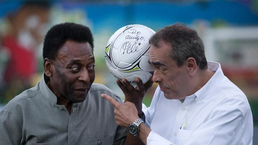 Brazilian soccer great Pele, left, and President of Shell Brazil Andre Araujo pose with a soccer ball during the inauguration of a soccer pitch to be powered by player's footsteps at the Morro da Mineira favela, in Rio de Janeiro, Brazil, Wednesday, Sept. 10, 2014. The project, sponsored by British oil giant Shell, has around 200 energy-capturing tiles installed along the width and breadth of the field and covered by a layer of AstroTurf. Working in conjunction with solar panels also installed around the field, the player-powered tiles feed electricity to a system of floodlights overhead. (AP Photo/Silvia Izquierdo)