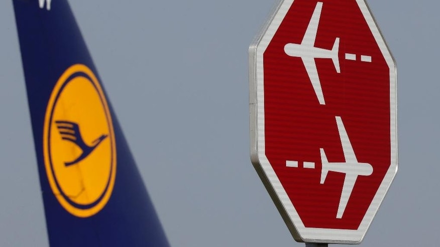 A Lufthansa aircraft passes a signpost at the airport in Munich during an eight-hour warning strike of Lufthansa pilots in Munich, southern Germany, Wednesday, Sept. 10, 2014. (AP Photo/Matthias Schrader)