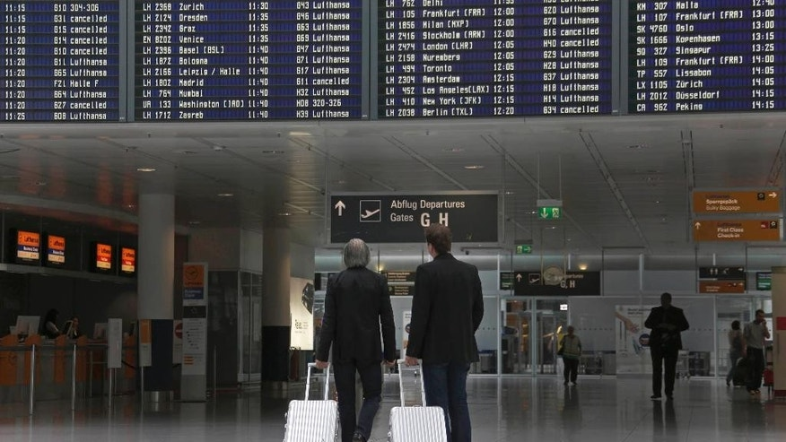 Passengers look at the flight board at an airport terminal before pilots of Lufthansa go on an eight-hour warning strike at Munich Airport in Munich, southern Germany, Wednesday, Sept. 10, 2014. (AP Photo/Matthias Schrader)