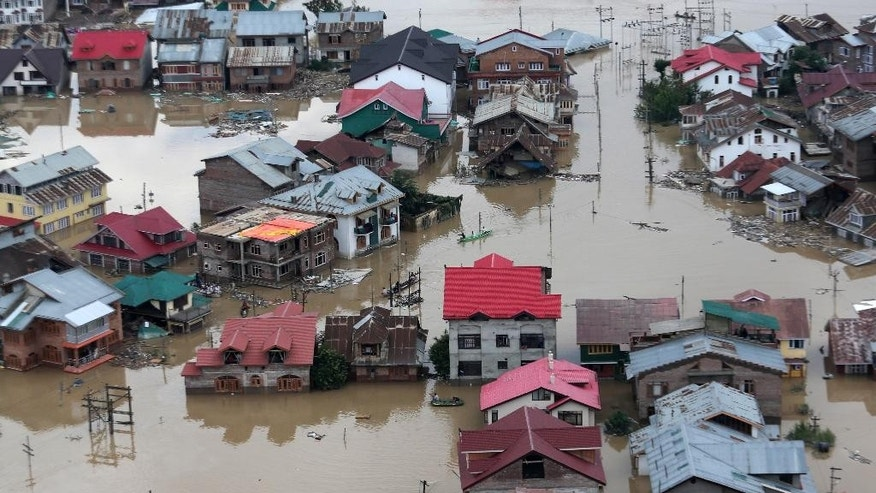 Flood-affected people row boats past partially submerged buildings in floodwaters in Srinagar, India, Tuesday, Sept. 9, 2014. The death toll from floods in Pakistan and India reached 400 on Tuesday and have put more than half a million people in peril and rendered thousands homeless in the two neighboring states. (AP Photo/Dar Yasin)