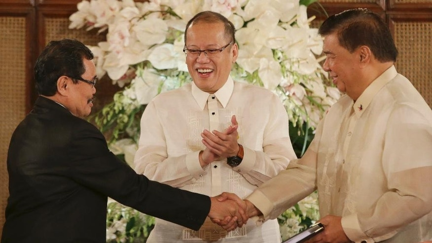 Philippine President Benigno Aquino III, center, claps as Moro Islamic Liberation Front chief negotiator Mohagher Iqbal, left, shakes hands with Senate President Franklin Drilon, right, as he turnover the Draft of the Bangsamoro Basic Law at the Malacanang Presidential Palace in Manila, Philippines on Wednesday, Sept. 10, 2014.  The Bangsamoro Basic Law is part of government efforts to end the decades-old conflict in southern Philippines. (AP Photo/Aaron Favila)