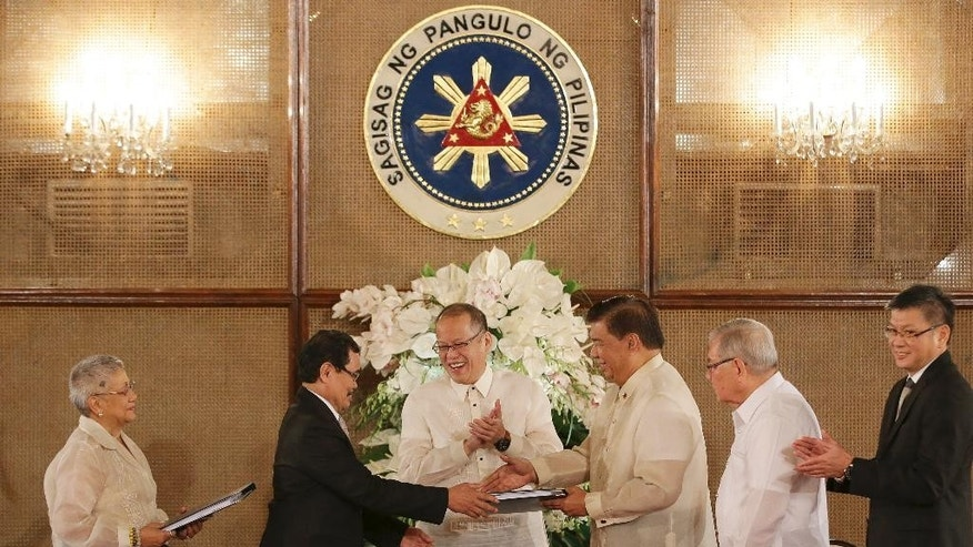 Philippine President Benigno Aquino III, 3rd from left, applauds as Moro Islamic Liberation Front chief negotiator Mohagher Iqbal, 2nd left, turnovers the Draft of the Bangsamoro Basic Law to Senate President Franklin Drilon, 3rd from right, during ceremonies at the Malacanang Presidential Palace in Manila, Philippines on Wednesday, Sept. 10, 2014.  The Bangsamoro Basic Law is part of government efforts to end the decades-old conflict in southern Philippines. (AP Photo/Aaron Favila)