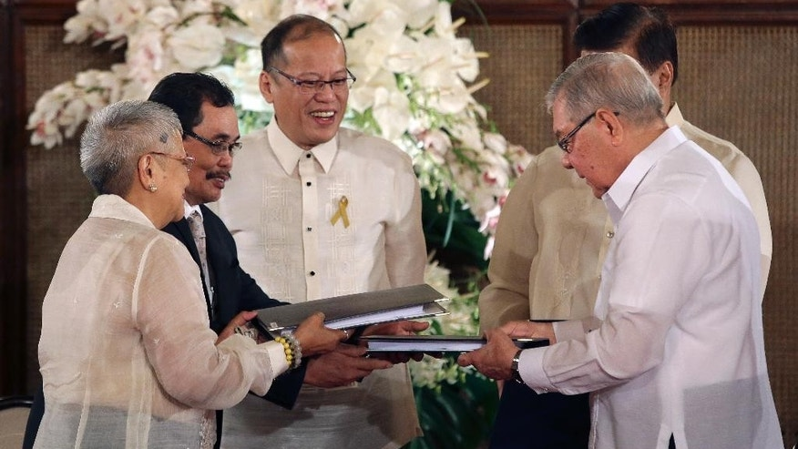 Philippine President Benigno Aquino III, center, watches Moro Islamic Liberation Front chief negotiator Mohagher Iqbal, 2nd left, and Presidential adviser on the peace process, Secretary Teresita Quintos-Deles, left, turning over the Draft of the Bangsamoro Basic Law to House Speaker Feliciano Belmonte, right, and Senate President Franklin Drilon, partly hidden, during ceremonies at the Malacanang Presidential Palace in Manila, Philippines on Wednesday, Sept. 10, 2014.  The Bangsamoro Basic Law is part of government efforts to end the decades-old conflict in southern Philippines. (AP Photo/Aaron Favila)