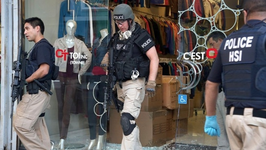 Law enforcement agents leave a clothing store after a raid in the Los Angeles Fashion District Wednesday, Sept. 10, 2014.  U.S. agents raided dozens of businesses in the fashion district of Los Angeles early Wednesday as part of an investigation into suspected money laundering done for Mexican drug cartels.  (AP Photo/ Nick Ut )
