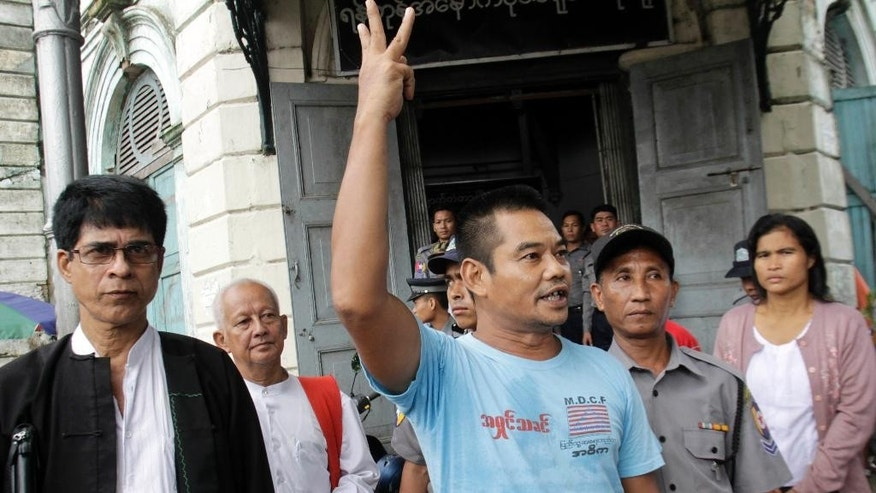 In this photo taken on Aug. 4, 2014, activist Htin Kyaw, right, shouts as he leaves a district court along with his lawyer Robert San Aung, left, after his trial in Yangon, Myanmar. A Myanmar court has sentenced the prominent human rights activist to two years in prison for marching through its biggest city and handing out leaflets that questioned the legitimacy of the country's new, nominally civilian government.  (AP Photo/Khin Maung Win)