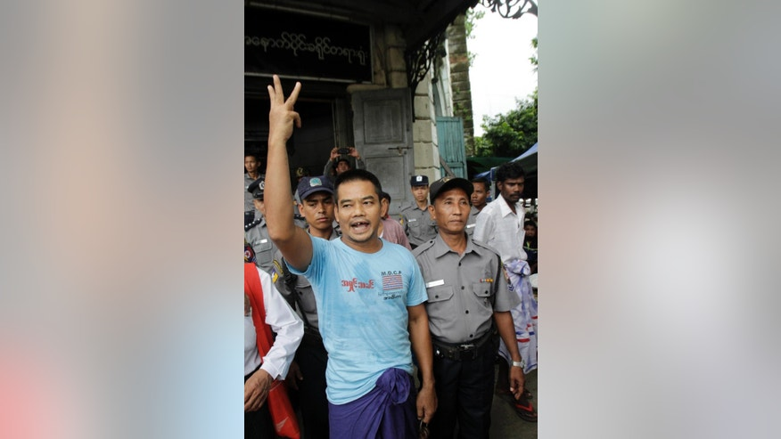 In this photo taken on Aug 4, 2014, activist Htin Kyaw, left, shouts as he is escorted by Myanmar polices after his trial at a district court in Yangon, Myanmar. A Myanmar court has sentenced the prominent human rights activist to two years in prison for marching through its biggest city and handing out leaflets that questioned the legitimacy of the country's new, nominally civilian government.  (AP Photo/Khin Maung Win)