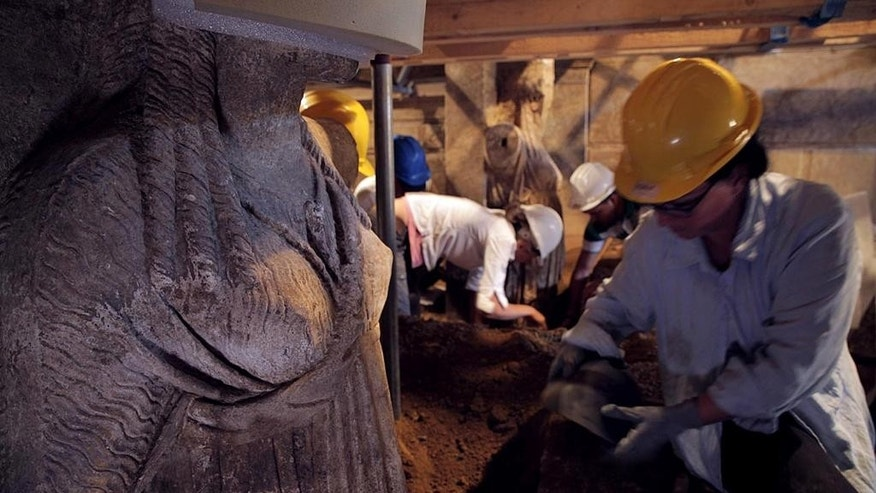 In this photo released on Thursday, Sept. 11, 2014 by the Greek Culture Ministry, excavation staff work between two approximately life-sized female statues on a wall leading to a yet unexplored inner room of a huge underground ancient tomb, in Amphipolis, northern Greece. The tomb dates between 325 B.C. — two years before the death of ancient Greek warrior-king Alexander the Great — and 300 B.C. Archaeologists have also discovered two large marble sphinxes on the facade of the barrel-vaulted tomb, which was originally topped by a marble lion on a high plinth. It is not yet  known who the tomb was built for, although Alexander himself was buried in Egypt. (AP Photo/Culture Ministry)