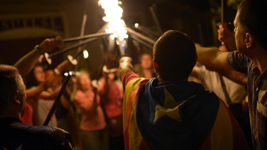 People burn torches during a march for the independence of Catalonia in Barcelona, Spain, Wednesday, Sept. 10, 2014. After years of mass protests by Catalans demanding the right to decide whether they want to break away from Spain and form a new European nation, the wealthy northeastern region's lawmakers are voting to ask permission from Spanish authorities to hold a secession referendum in November. (AP Photo/Manu Fernandez)