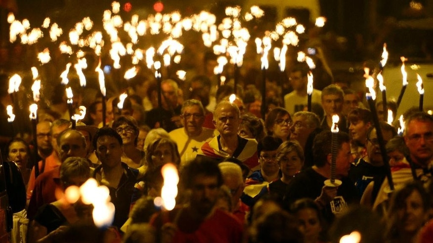 People hold torches during a march for the independence of Catalonia in Barcelona, Spain, Wednesday, Sept. 10, 2014. After years of mass protests by Catalans demanding the right to decide whether they want to break away from Spain and form a new European nation, the wealthy northeastern region's lawmakers are voting to ask permission from Spanish authorities to hold a secession referendum in November. (AP Photo/Manu Fernandez)