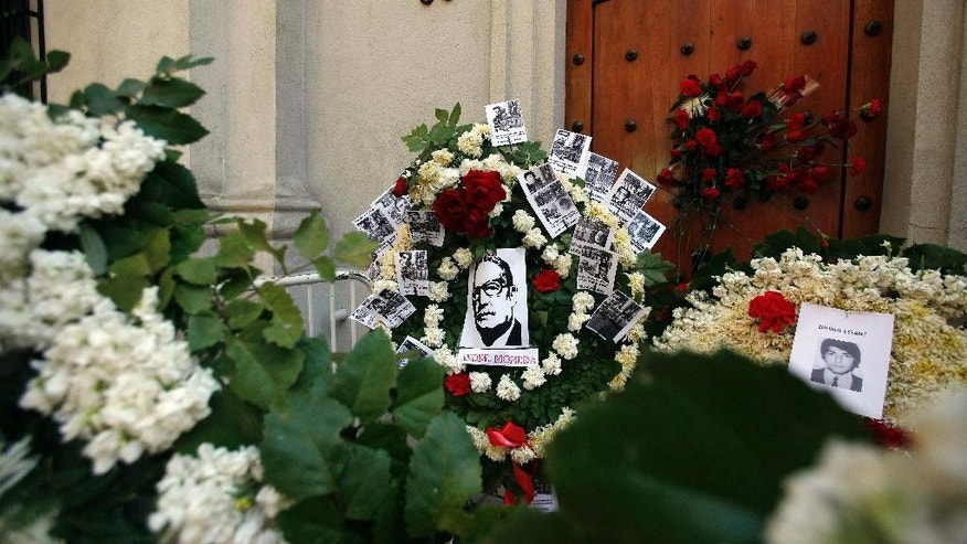 """Images of """"desaparecidos,"""" or """"disappeared ones,"""" and the late Chilean President Salvador Allende, are attached to flower wreaths placed in front of the east side entrance of La Moneda presidential palace, referred to by it's street address, Morande 80, to mark the 41st anniversary of Chile's 1973 military coup, in Santiago, Chile, Thursday, Sept. 11, 2014. The coup toppled Allende and began the military dictatorship of Gen. Augusto Pinochet. Allende used the side entrance to enter and leave the palace. It was also through this door that his body was carried by soldiers and firefighters from the destroyed presidential palace after the coup. (AP Photo/Luis Hidalgo)"""