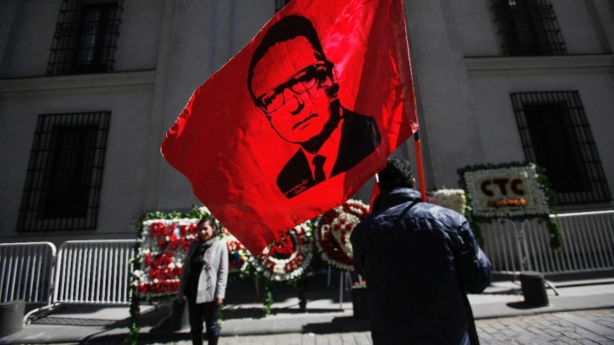 A man holds a flag with the portrait of late Chile's president Salvador Allende in front of the east side entrance of La Moneda presidential palace, referred to by it's street address, Morande 80, in Santiago, Chile, Thursday, Sept. 11, 2014. The coup toppled Chilean President Salvador Allende and began the military dictatorship of Gen. Augusto Pinochet. Allende used the side door to enter and leave the palace. It was also through this door his body was carried by soldiers and firefighters from the destroyed presidential palace after the coup. (AP Photo/Luis Hidalgo)