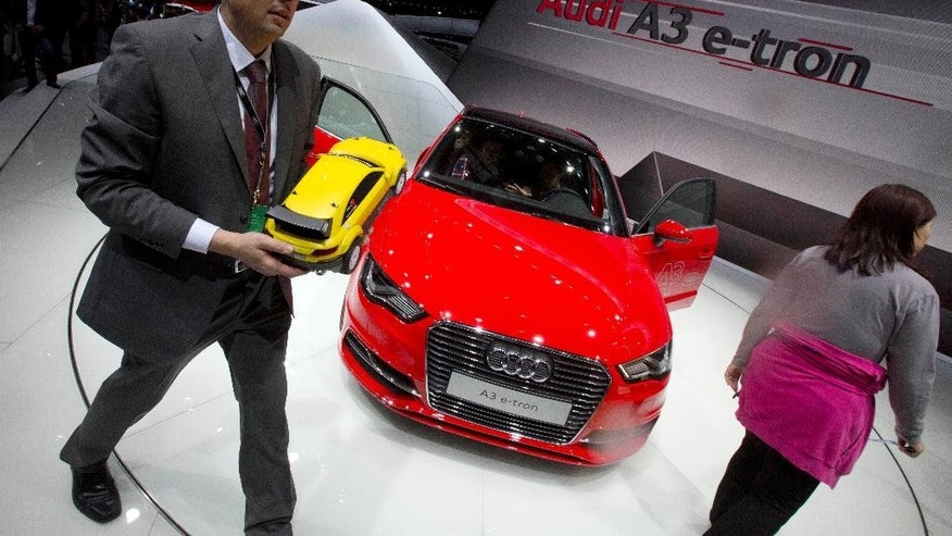 FILE - In this April 20, 2014 file photo, a man holds a scaled model of a Audi car as he walks past the Audi A3 e-tron displayed at the China Auto show in Beijing, China. China on Thursday, Sept. 11, 2014, announced it will fine automaker Audi $40.5 million and Chrysler $5.2 million in a sweeping anti-monopoly probe of their industry that has prompted complaints foreign businesses are being treated unfairly. (AP Photo/Ng Han Guan, File)