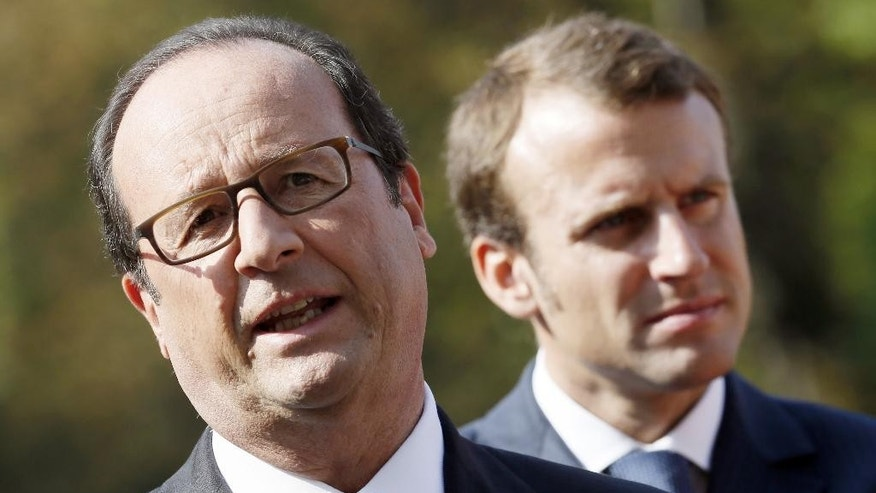 "French President François Hollande, left, poses Economy Minister Emmanuel Macron following the presentation of the ""34 plans for the new industrial France"" Tuesday, Sept. 9, 2014 at the Elysee Palace in Paris. (AP Photo/Patrick Kovarik, Pool)"