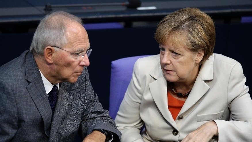 German Chancellor Angela Merkel, right, and German Finance Minister Wolfgang Schaeuble, left, talk during a meeting of the German parliament, Bundestag, in Berlin, Germany, Thursday, Sept. 11, 2014. (AP Photo/Michael Sohn)