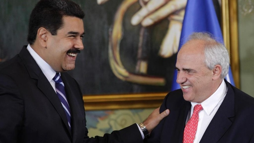 Venezuela's President Nicolas Maduro smiles with newly sworn-in General Secretary of the Union of South American Nations, Colombia's former President Ernesto Samper, during a transfer ceremony at the Miraflores Presidential Palace in Caracas, Venezuela, Thursday, Sept. 11, 2014. Samper, who the U.S. stripped of his visa two decades ago for taking payments from the nation's biggest drug cartel is making a political comeback as a promoter of South American solidarity. (AP Photo/Ariana Cubillos)
