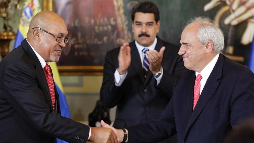 Venezuela's President Nicolas Maduro applauds, center, as outgoing General Secretary of the Union of South American Nations and President of Surinam Desire Bouterse, left, shakes hands with the incoming general secretary, Colombia's former president Ernesto Samper, during a transfer ceremony at the Miraflores Presidential Palace in Caracas, Venezuela, Thursday, Sept. 11, 2014. Samper, who the U.S. stripped of his visa two decades ago for taking payments from the nation's biggest drug cartel is making a political comeback as a promoter of South American solidarity. (AP Photo/Ariana Cubillos)