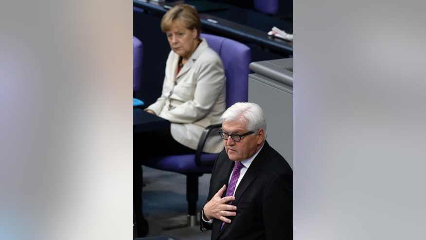 German Chancellor Angela Merkel, rear, attends the speech of German Foreign Minister Frank-Walter Steinmeier, front, during a meeting of the German parliament, Bundestag, in Berlin, Germany, Thursday, Sept. 11, 2014. (AP Photo/Michael Sohn)