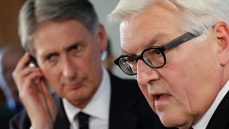 German Foreign Minister Frank-Walter Steinmeier, right, and his counterpart from Britain, Philip Hammond, left, address the media during a joint press conference after a meeting in Berlin, Germany, Thursday, Sept. 11, 2014. (AP Photo/Michael Sohn)