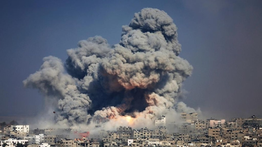 FILE - In this July 29, 2014 file photo, smoke and fire from the explosion of an Israeli strike rise over Gaza City. The Israeli military said Wednesday, Sept. 10, it has opened criminal investigations into two high-profile cases involving Palestinian civilian casualties in this summer's Gaza war, in an apparent attempt to head off international investigations into its conduct. (AP Photo/Hatem Moussa, File)