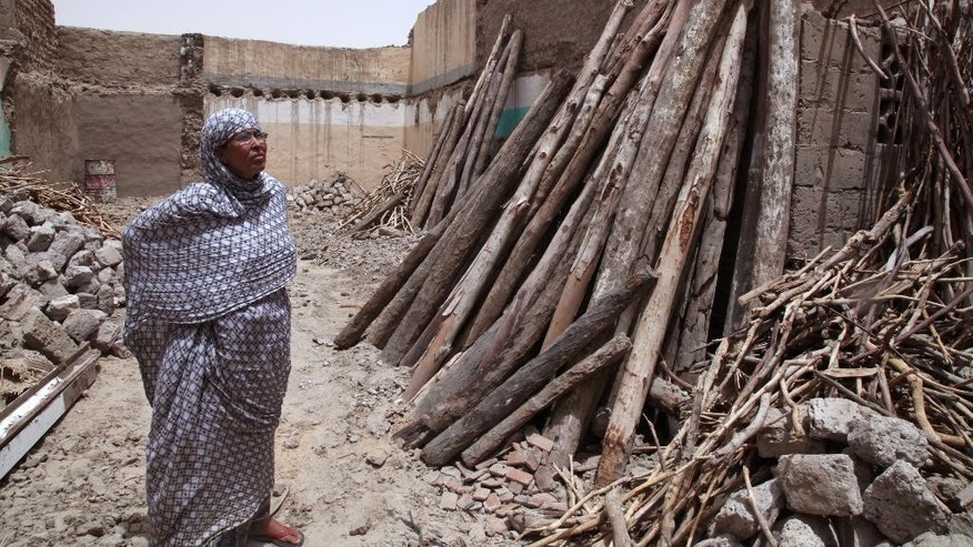 In this photo taken Tuesday, Aug. 26, 2014,  Fadimata Walet Abdou Salam stands inside her home were she lived before becoming a refugee in Timbuktu, Mali. A pile of stones and wood was all that remained of the house where Fadimata Walet Abdou Salam once lived when she and her young daughters returned after more than a year of sleeping in a tent as refugees in a foreign country. Looters had stolen the windows and doors, and then heavy rains transformed the earthen walls into a heap of mud after she had to abandon her home in Timbuktu following unrest and violence. (AP Photo/Baba Ahmed)