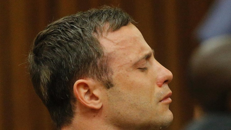 Oscar Pistorius reacts in the dock in Pretoria, South Africa, Thursday Sept. 11, 2014 as Judge Thokozile Masipa reads notes as she delivers her verdict in Pistorius' murder trial. The South African judge in Oscar Pistorius' murder trial said Thursday that prosecutors have not proved beyond a reasonable doubt that the double-amputee Olympic athlete is guilty of premeditated murder. (AP Photo/Kim Ludbrook, Pool)