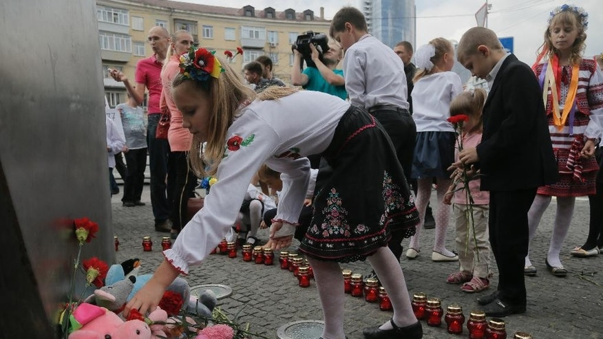 Ukrainians children lay flowers and toys on the monument of victims of terror during a remembrance ceremony in memory of the Sept. 11 terror attacks  in the United States and  memory of the people, who died during the Boeing 777, Malaysia Airlines flight MH17 crash in eastern Ukraine in Kiev, Ukraine, Thursday, Sept. 11, 2014. (AP Photo/Efrem Lukatsky)