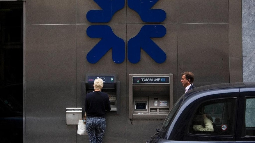 A woman uses a Royal Bank of Scotland (RBS) cash machine with an RBS logo above it, in the City of London, Thursday, Sept. 11, 2014.  In a blow to the Scottish independence campaign, three top financial groups, including the Royal Bank of Scotland, say they will move headquarters to England should Scots vote to break away from the United Kingdom.  RBS, which has been based in Scotland since 1727, said Thursday it has drawn up contingency plans because being based in an independent Scotland would create uncertainties that could hurt its business and customers.  (AP Photo/Matt Dunham)