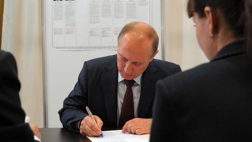 Russian President Vladimir Putin signs papers as he prepares to vote in a local election in Moscow, Russia, Wednesday, Sept. 10, 2014. President Vladimir Putin said Wednesday that Russia will develop an array of new nuclear and conventional weapons to counter recent moves by the U.S. and NATO. (AP Photo/RIA-Novosti, Alexei Druzhinin, Presidential Press Service)