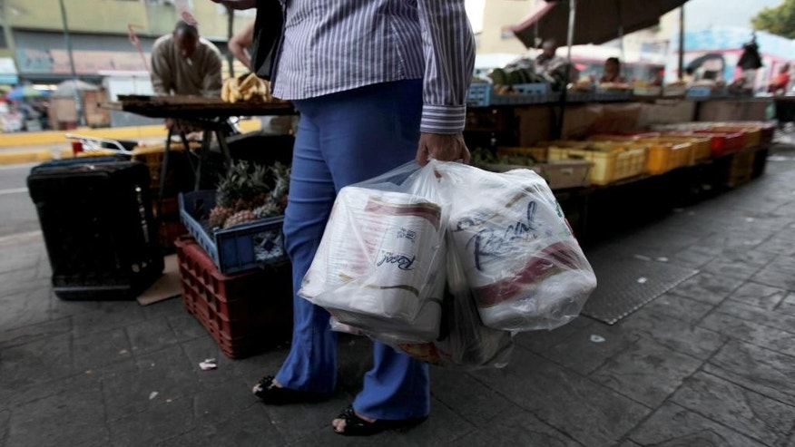 FILE- In this May 15, 2013 file photo, a woman who just bought toilet paper at a grocery store reads her receipt as she leaves the private store in Caracas, Venezuela. On Wednesday Sept. 10, 2014, Venezuela's President Nicolas Maduro reassured foreign creditors that his government will make good on a $4.5 billion foreign debt payment due next month. (AP Photo/Fernando Llano, File)