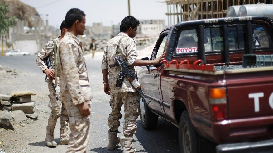 Yemeni army soldiers check a vehicle at a checkpoint while guarding the entrance of Sanaa, Yemen, Wednesday, Sept. 10, 2014. Tensions have been escalating in the Yemeni capital, where the Hawthis have staged weekslong anti-government demonstrations, often clashing with the police forces and demanding that the government reinstate fuel subsidies and then resign. (AP Photo/Hani Mohammed)