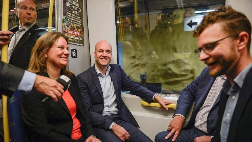 Prime Minister Fredrik Reinfeldt, center, rides the Stockholm subway with local politician Cecilia Lofgren, left, and campaign workers Thursday, Sept. 11, 2014. Sweden will head to the polls Sunday, in an election that is expected to be closely fought. (AP Photo/TT, Jessica Gow)  SWEDEN OUT