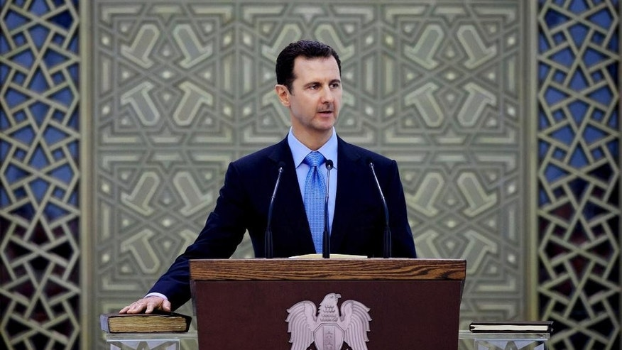 FILE - In this Wednesday, July 16, 2014 file photo released by the Syrian official news agency SANA, Syria's President Bashar Assad is sworn for his third, seven-year term, in Damascus, Syria. The Syrian government has said it welcomes U.S. airstrikes against the Islamic State group in Syria. But it had been gambling that Washington would partner with it against the extremists, hoping for a dramatic reversal in the U.S. policy calling for Assad's removal. (AP Photo/SANA, File)