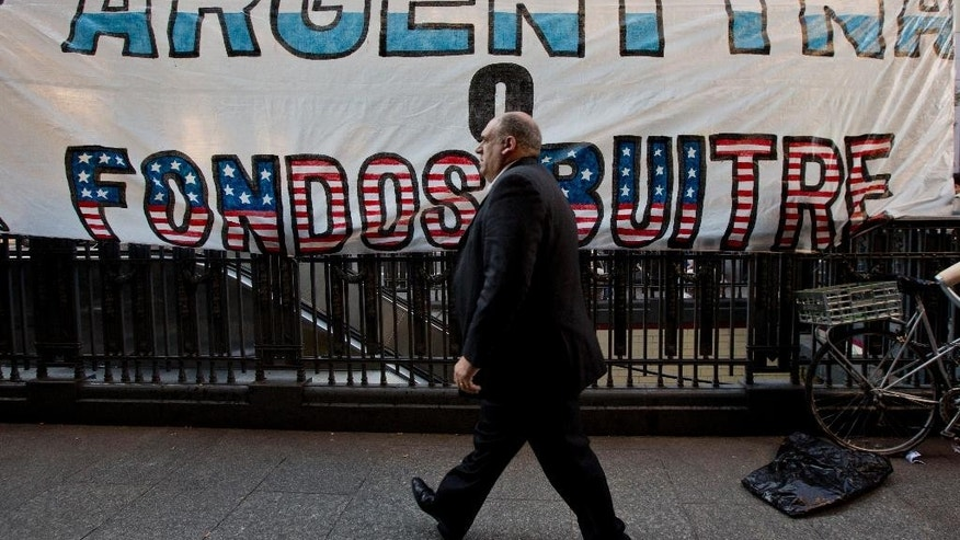 "A man walks by a banner that reads in Spanish ""Argentina or vulture funds"" outside Congress in Buenos Aires, Argentina, Wednesday, Sept. 10, 2014. Congress is expected to vote on a bill, that if approved, would allow the Argentine government to pay creditors locally in Argentina, sidestepping the U.S. financial system to avoid U.S. court jurisdiction. Argentina was forced into a second default on July 30 following a decade-long legal battle with U.S. investors including hedge funds who refused to accept lower payments for bonds that the South American country defaulted on in 2001. The investors obtained a U.S. court order, preventing Argentina from making interest payments which triggered the second default. (AP Photo/Natacha Pisarenko)"