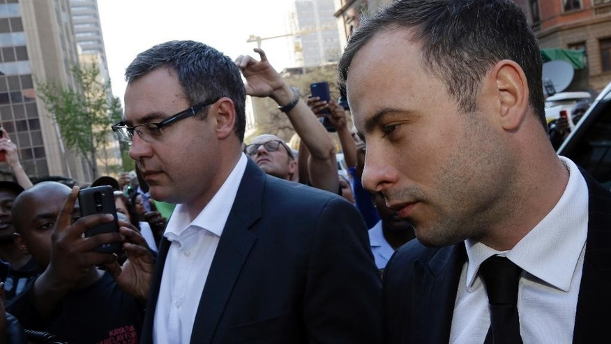 Oscar Pistorius, right, arrives at the high court in Pretoria, South Africa, Friday, Sept. 12, 2014. Presiding Judge Thokozile Masipa is expected to announce her verdict in Pistorius' murder trail after scrutinizing evidence Thursday and Friday given by 37 witnesses in a court transcript running to thousands of pages in a drama that has played out over six months. (AP Photo/Themba Hadebe)