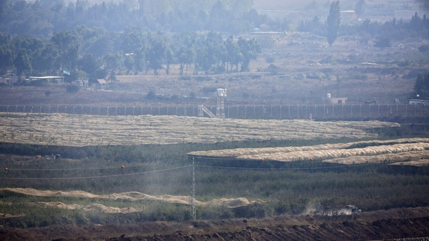 Sept. 1, 2014 - An Israeli army jeep drives near the Quneitra crossing in the Israeli-controlled Golan Heights, overlooking the border with Syria. Dozens of reserve soldiers from an elite Israeli intelligence unit have sent a letter to the country's military chief and prime minister saying they refuse to serve for moral reasons.