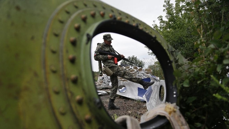 "AP10ThingsToSee- A Pro-Russian rebel looks at pieces of the Malaysia Airlines Flight 17 plane near village of Rozsypne, eastern Ukraine, Tuesday, Sept. 9, 2014. The Dutch team investigating the downing of Malaysia Airlines Flight 17 over Eastern Ukraine says the crash was likely caused by the plane being hit by multiple ""high-energy objects from outside the aircraft."" (AP Photo/Sergei Grits)"