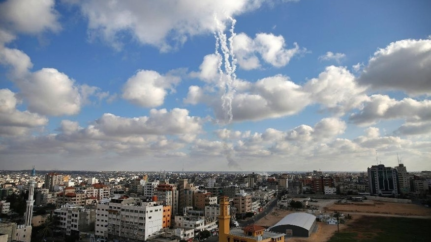 FILE - In this July 18, 2014 file photo, smoke trails behind multiple missiles fired at Israel from the Gaza Strip. Two weeks after the end of the Gaza war, there is growing evidence that Hamas militants used residential areas as cover for launching rockets at Israel, at least at times. But Hamas says that a heavy-handed Israeli response is to blame for the deaths of hundreds of Palestinian civilians. (AP Photo/Lefteris Pitarakis, File)