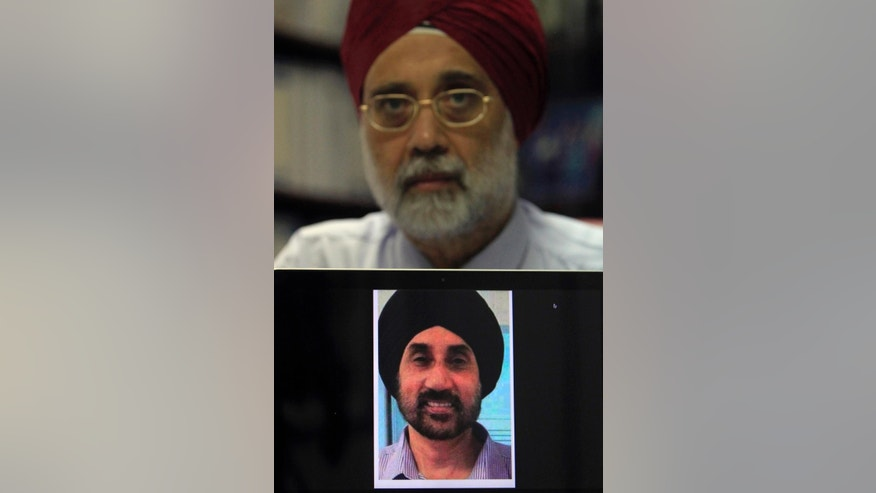 "In this Sept. 11, 2014 photo, Rajindar Singh, 65, brother of Karamjit Singh, who died when Malaysia Airlines Flight 17 was shot down over eastern Ukraine on July 17, shows his late brother's photo during an interview at his specialist clinic in Teluk Intan, Perak state, Malaysia. Rajindar Singh is urging authorities to speed up their probe into the accident. He wants the answer to one question: ""Who actually pulled the trigger?"" (AP Photo/Lai Seng Sin)"