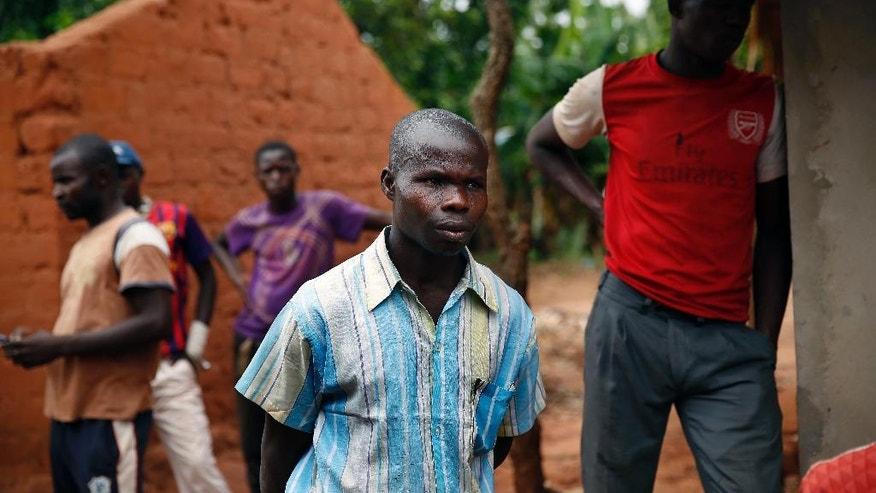 In this April 15, 2014, photo, Anti-Balaka Christian men stand at the front of a looted Muslim store in Guen, some 250 kilometers north of Bangui, Central African Republic.  More than 5,000 people have died in sectarian violence in the Central African Republic since December, according to an Associated Press tally. (AP Photo/Jerome Delay)