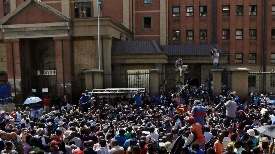 Bystanders and journalists surround a vehicle carrying Oscar Pistorius as he leaves the high court in Pretoria, South Africa, Friday, Sept. 12, 2014.  Judge Thokozile Masipa found Pistorius guilty of culpable homicide for the shooting death of his girlfriend Reeva Steenkamp. (AP Photo/Themba Hadebe)