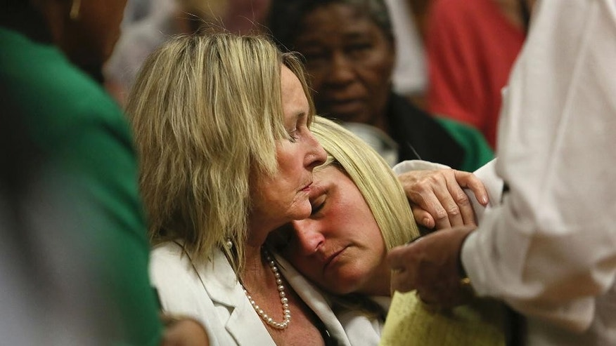 Mother and cousin of the late Reeva Steenkamp, June Steenkamp, left, and Kim Martin, right, comfort one another in court in Pretoria, South Africa, Friday, Sept. 12, 2014.  In passing judgement judge Thokozile Masipa  ruled out a murder conviction for the double-amputee Olympian in the shooting death of his girlfriend, Reeva Steenkamp,  but said he was negligent and convicted him of culpable homicide. (AP Photo/Alon Skuy, Pool)