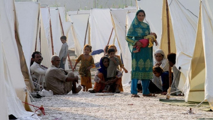 Pakistani flood affected villagers settle in a relief camp in Jhang, Pakistan, Thursday, Sept. 11, 2014. Pakistani troops used helicopters and boats to evacuate thousands of marooned people from the country's plains where raging monsoon floods inundated more villages Thursday, officials said. (AP Photo/K.M. Chaudary)